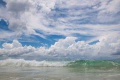 Sandig strand med klart vatten och härlig blå himmel med moln Arkivbilder