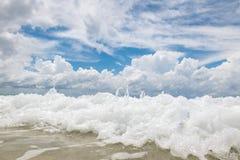 Sandig strand med klart vatten och härlig blå himmel med moln Arkivbild