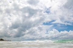 Sandig strand med klart vatten och härlig blå himmel med moln Royaltyfri Foto