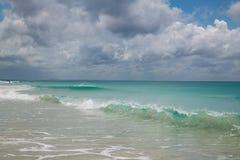 Sandig strand med klart vatten och härlig blå himmel med moln Arkivfoto