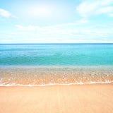 Sandig strand med lugna vatten mot blåa himlar Royaltyfri Bild