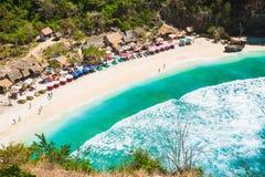 Sandig strand med turkoshavet och ljusa färgrika paraplyer, Nusa Penida royaltyfri fotografi