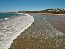 Sandig strand med vita havvågor och blå himmel Royaltyfri Foto