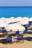 Sandig strand med vita slags solskydd och sunbeds Arkivbilder