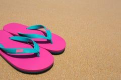 sandig strand och rosa sandaler royaltyfri fotografi