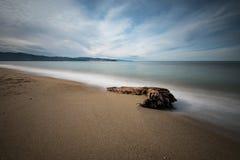Sandig strand och sten i havet arkivbild
