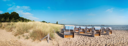 Sandig strand och traditionella trästrandstolar på ön Rugen fotografering för bildbyråer