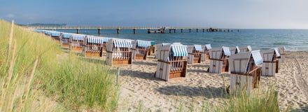 Sandig strand och traditionella trästrandstolar på ön Rugen royaltyfria foton