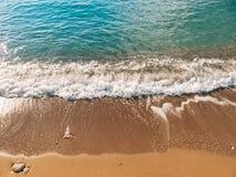 Sandig strand och vågor, närbild Textur av sand och vatten pict arkivfoton