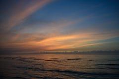 Sandig strand på en bakgrund av solnedgången och himmel med moln Arkivbild
