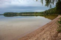Sandig strand på en sjö i en skog Royaltyfri Fotografi