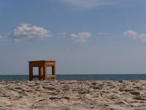 Sandig strand, stol och hav Royaltyfri Bild