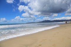 Sandig strand under blå himmel Arkivbilder