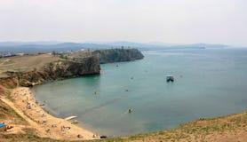 Sandig strand vid sjön med massor av holidaymakers arkivbilder