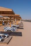 Sandig tropisk strand med chaisevardagsrum Royaltyfri Foto