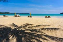 Sandig tropisk strand med solstolar Fotografering för Bildbyråer