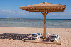 Sandig tropisk strand med två chaisevardagsrum Royaltyfri Bild