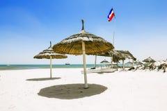 Sandiga stränder med slags solskydd på det medelhavs- i Tunisien Royaltyfri Bild
