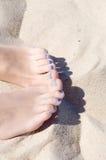 Sandige Füße der Frau mit Blau nagelt Pediküre Stockbild