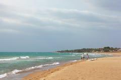 Sandiger Strand der Sommerseeansicht, Wellen am sonnigen Tag Funkelnde Wellen, die auf dem Strand einhüllen Zwei Jugendliche gehe lizenzfreie stockfotos