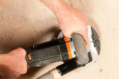 Sanding the cement floor. Construction worker working grinding the cement floor (only hand and machine to be seen royalty free stock photos