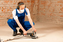 Sanding the cement floor. Construction worker working grinding the cement floor royalty free stock photos