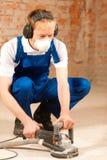 Sanding the cement floor. Construction worker working grinding the cement floor stock photo
