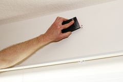 Sanding Down Hole in Wall. Hand reaching up near ceiling with a black sanding sponge pad to ground down the edges of a hole in the wall in order to patch it more Royalty Free Stock Photos