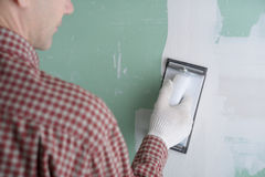 Sanding the drywall mud. Contractor sanding the drywall mud using sand trowel Royalty Free Stock Photos