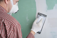 Sanding the drywall mud. Contractor sanding the drywall mud using sand trowel Royalty Free Stock Images