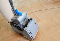Sanding hardwood floor with the grinding machine. Repair in the apartment. Carpenter doing parquet wood floor polishing maintenance work by grinding machine Royalty Free Stock Photos