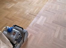 Sanding parquet with the grinding machine. Sanding hardwood floor with the grinding machine. Repair in the apartment. Carpenter doing parquet wood floor Royalty Free Stock Photo