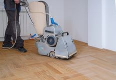 Sanding hardwood floor with the grinding machine. Repair in the apartment. Carpenter doing parquet wood floor polishing maintenance work by grinding machine stock image