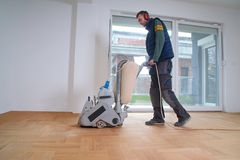 Sanding parquet with the grinding machine. Sanding hardwood floor with the grinding machine. Repair in the apartment. Carpenter doing parquet wood floor Royalty Free Stock Image