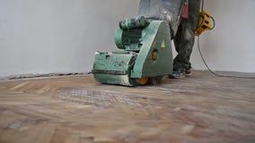 Sanding hardwood floor with the grinding machine. Repair in the apartment