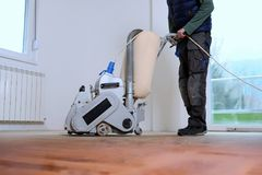 Sanding hardwood floor with the grinding machine. Repair in the apartment. Carpenter doing parquet wood floor polishing maintenance work by grinding machine Stock Photography