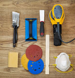 Sanding and Painting Accessories on Faded Wooden Boards. Overhead view of sanding and painting equipment positioned on rustic wooden boards.  Items include Stock Photo