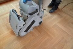 Sanding parquet with the grinding machine. Polishing, repair in. Sanding hardwood floor with the grinding machine. Repair in the apartment. Carpenter doing stock image