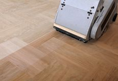 Sanding parquet with the grinding machineshing, repair in. Sanding hardwood floor with the grinding machine. Repair in the apartment. Carpenter doing parquet Stock Photo