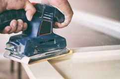 Orbital sander in use, sanding old door for a new lick of paint. Stock Photos