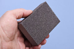 Sanding sponge in men`s hand Stock Photography