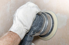 Sanding of a wall with a power sander Stock Photo
