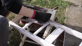 Sanding, women using sandpaper on an old chair. Outdoor stock video footage