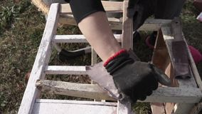 Sanding, women using sandpaper on an old chair. Outdoor stock footage