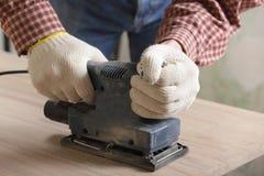 Sanding the wood. Carpenter sanding the wooden plank using power tool Stock Photo