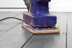 Sanding wood floorboard. Man sanding wooden floorboard with electric sander Stock Photography