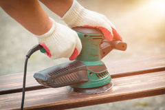 Sanding a wood with orbital sander Royalty Free Stock Photos