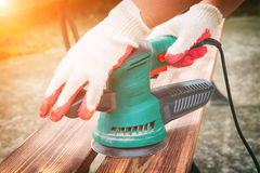 Sanding a wood with orbital sander. Outdoor Royalty Free Stock Photos
