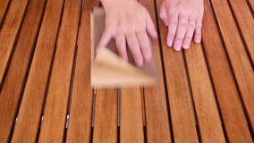 Sanding Wooden Table 1. Person sanding a wooden table by hand to prepare it for varnishing stock footage