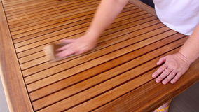 Sanding Wooden Table 2. Person sanding a wooden table by hand to prepare it for varnishing stock footage
